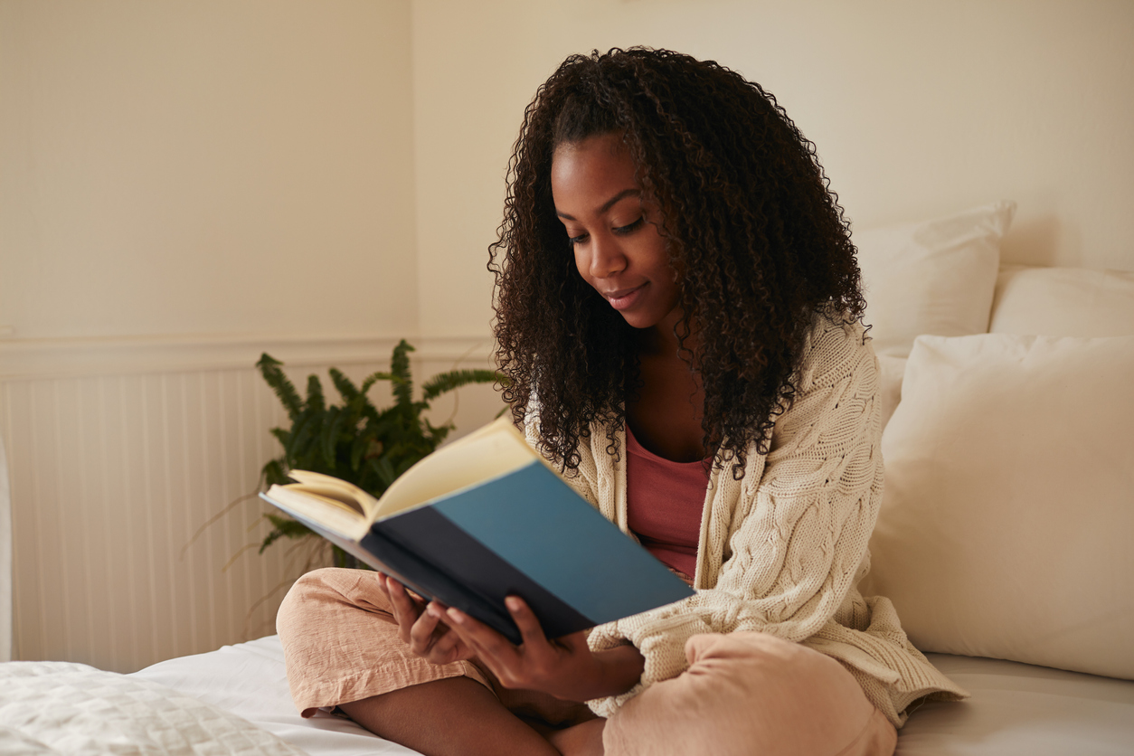 a woman sitting in bed reading a book