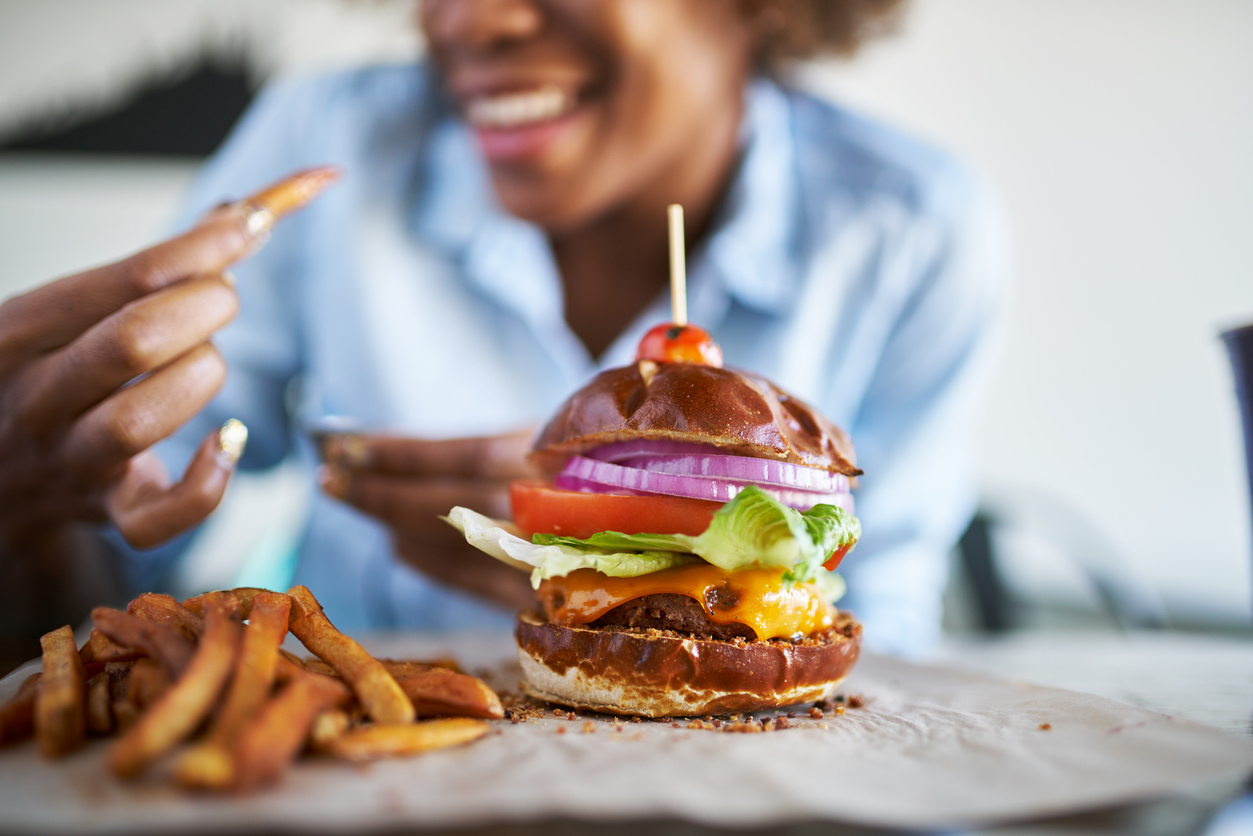 a burger and fries in front of a woman.