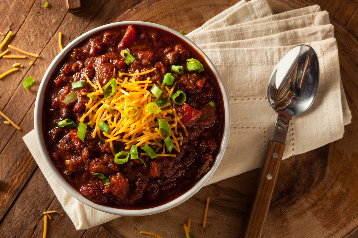 a bowl of chili next to a spoon