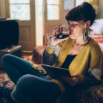 Woman drinking wine on her couch