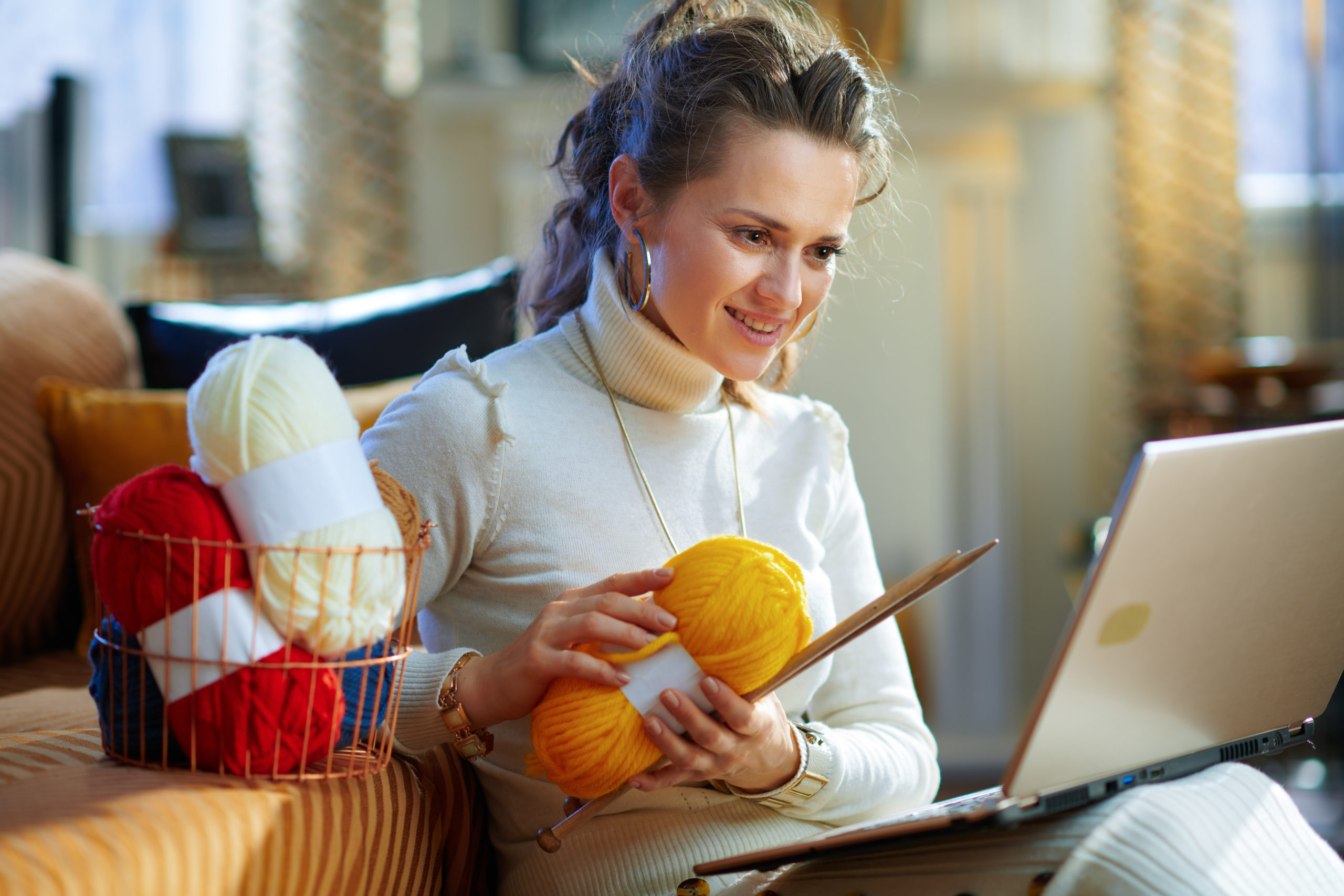 A woman participating in a virtual knitting event on her laptop.