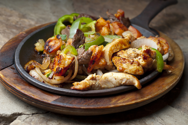 A skillet of fajitas with bell peppers and onions from an Ellicott City Mexican restaurant